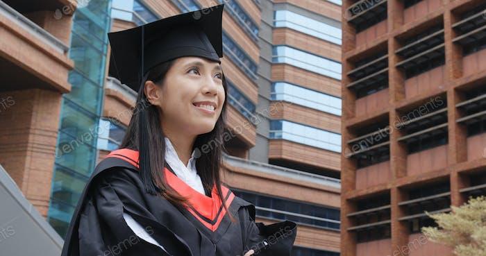 Cheerful confident graduation woman look far away