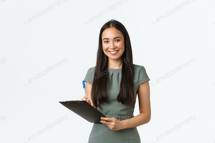 Smiling successful asian businesswoman writing down clients info, holding clipboard and pen, fill in