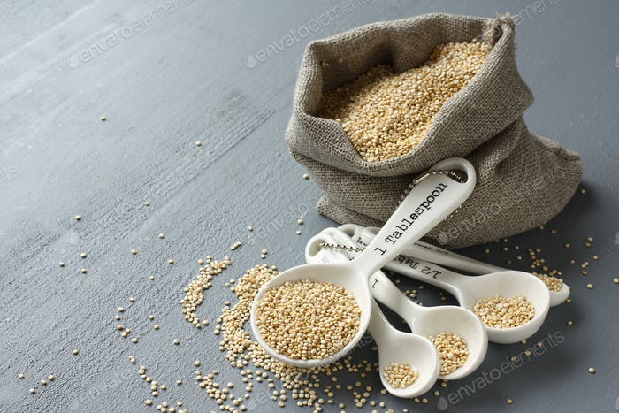 Quinoa grain in porcelain measuring spoons on gray background