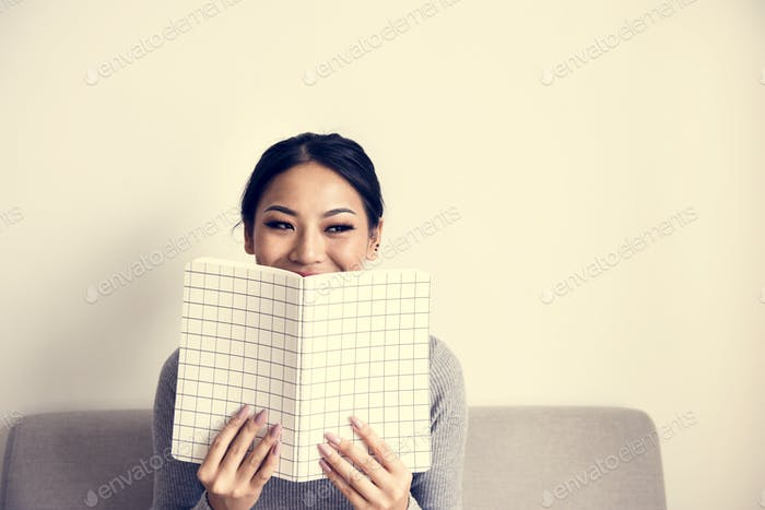 Woman face covered with notepad on white background