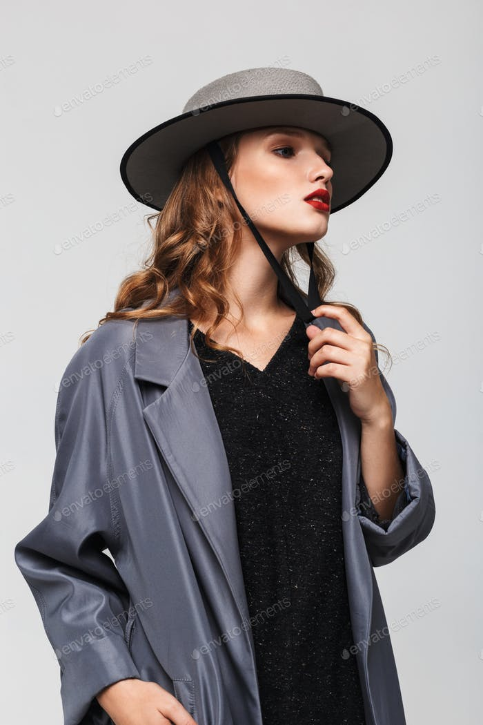 Young beautiful pensive woman with wavy hair in modern hat and cloak thoughtfully looking aside