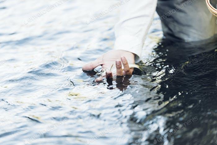Hand mit gefangenem Fisch.