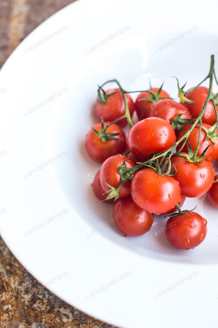 Reife frische rote Kirschtomaten auf weißem Hintergrund