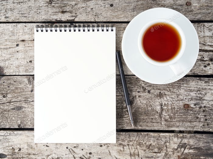 open notepad with clean white page, pen and coffee cup on aged old rustic wooden table, top view