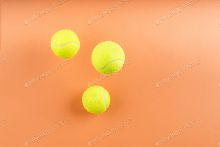 Tennis balls bouncing on orange. Concept