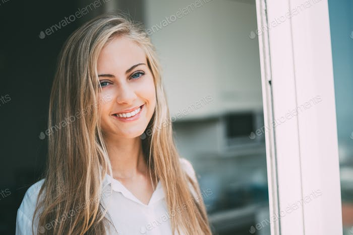 Young thoughtful woman looking through the window