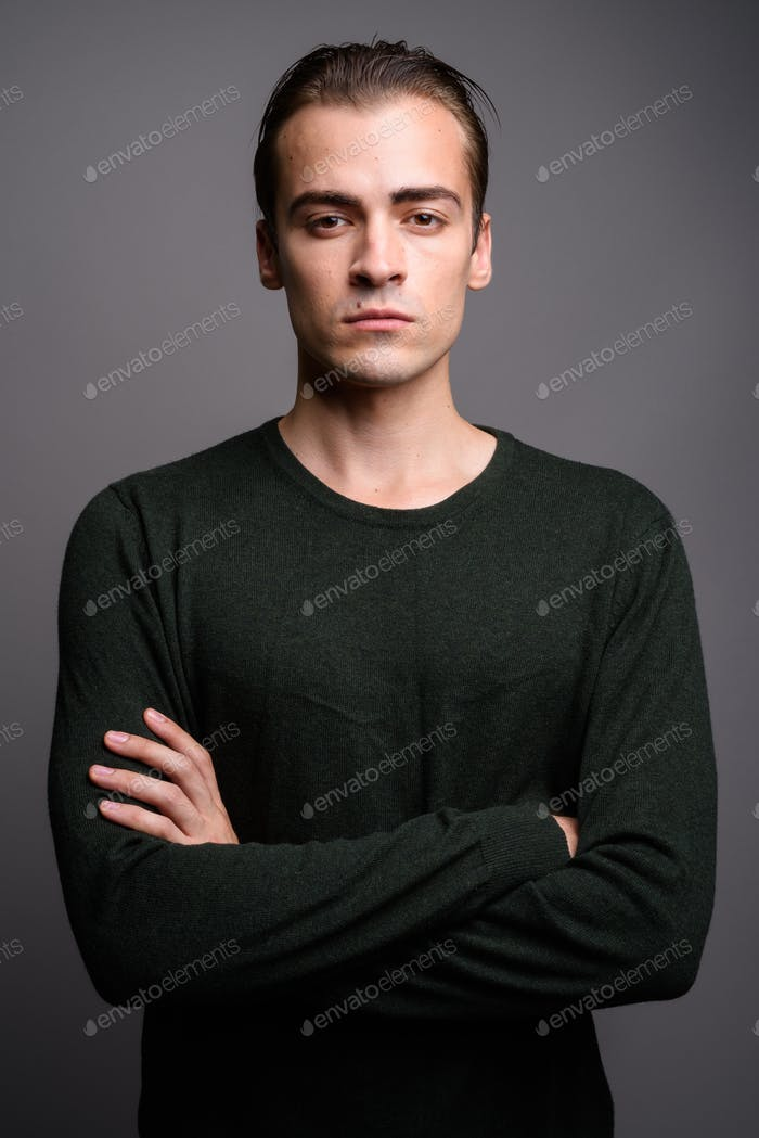 Young handsome man wearing green long sleeved shirt against gray
