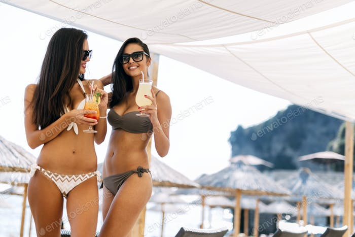 Beautiful women on beach enjoying cocktails