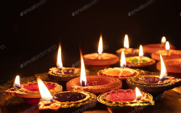 Diwali, Hindu festival of lights celebration. Diya oil lamps against dark background,