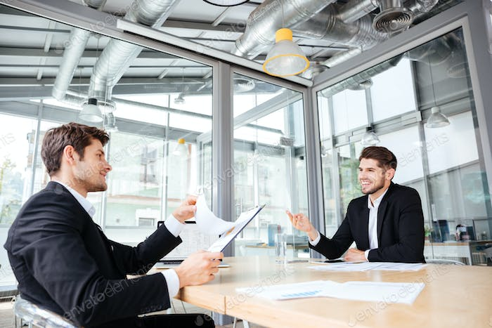 Two cheerful young businessmen creating business plan on meeting