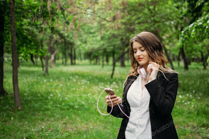 Language Learning, online study concept. Young girl in headphones and with a smartphone learns a