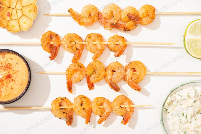 top view of delicious fried prawns on skewers with garlic, lime and sauces on white background