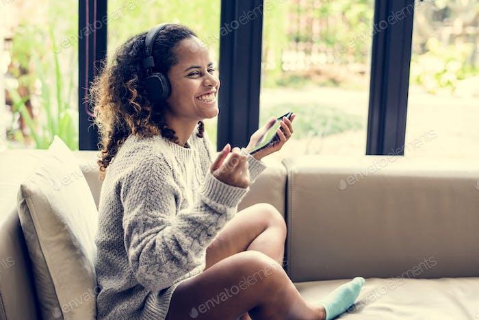 Frau genießen Musik auf ihrem Sofa