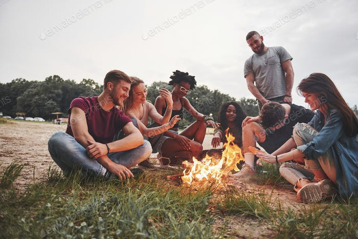 Young and cheerful friends. Group of people have picnic on the beach