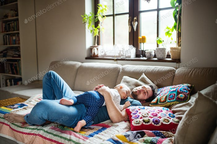 Father with a baby girl at home sleeping.