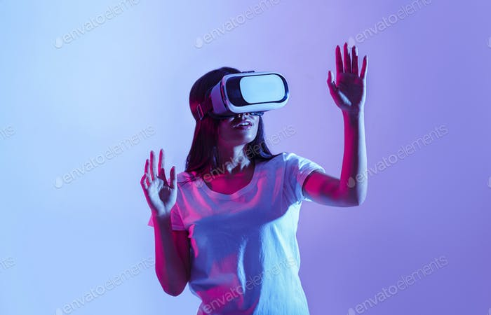 Modern device. Surprised asian girl in virtual glasses