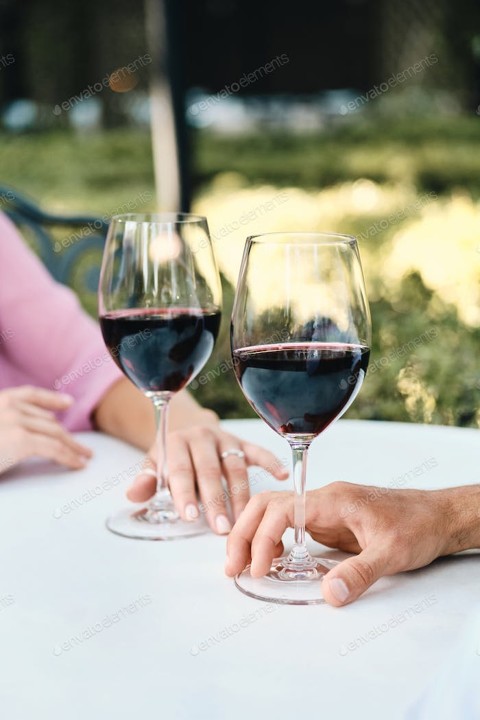 Close up photo of couple with glasses of red wine on romantic date in restaurant outdoor