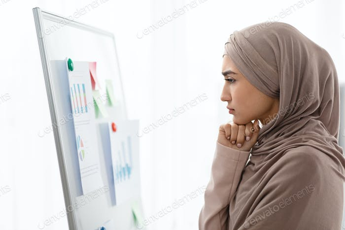 Concerned muslim business lady watching infographics at flip chart in office