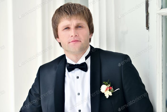 Handsome groom in suit in the nature