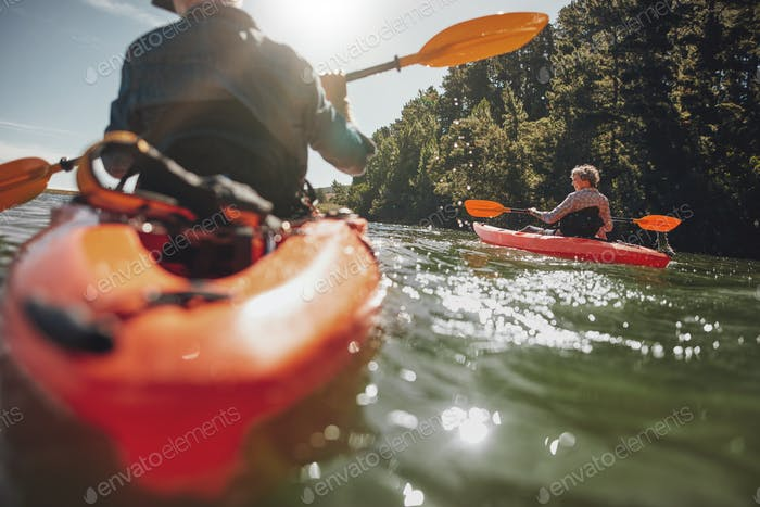 Mature woman kayaking in lake on a sunny day