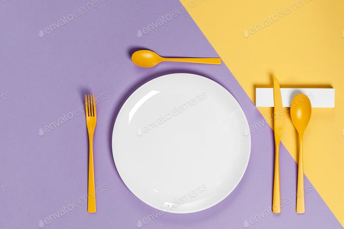 White utensils and yellow cutlery on a pastel colored background