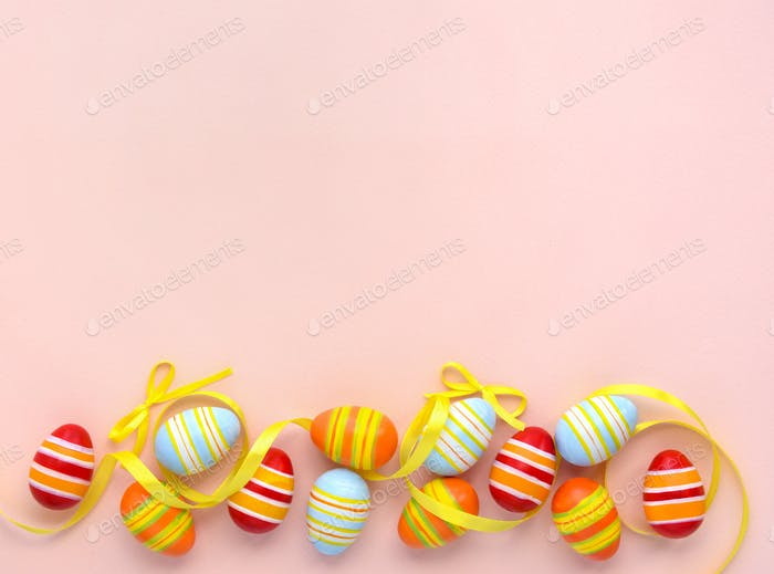 Colorful easter eggs and ribbons on a pink background with empty