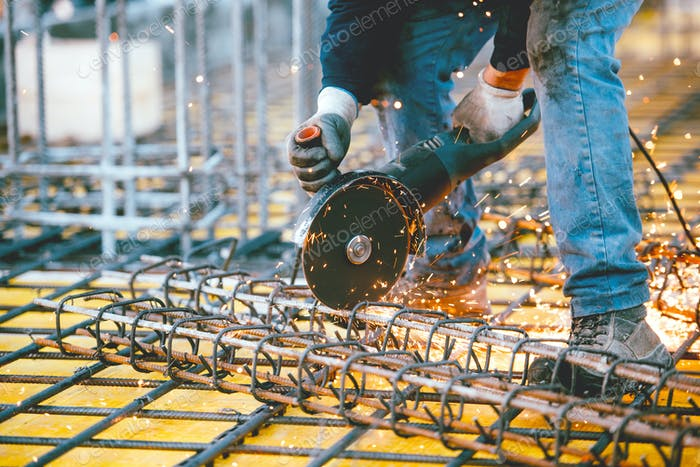 worker using an angle grinder for cutting steel, making sparks and debris