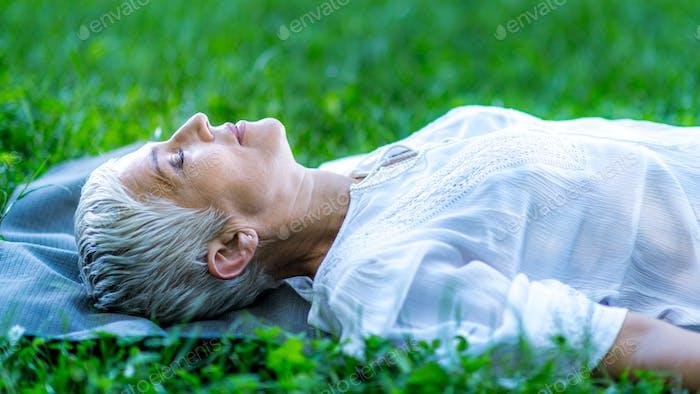 Achtsame Frau liegt am Wasser, meditieren