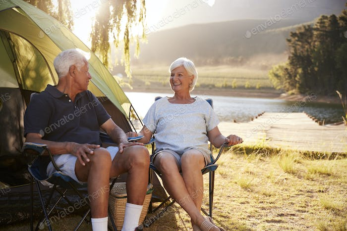 Senior Couple Enjoying Camping Vacation By Lake Together