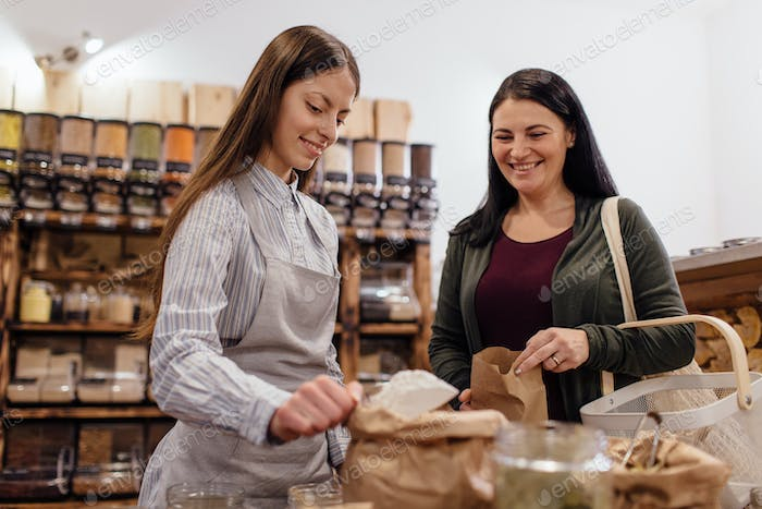 Zero waste shopping - woman buying flour at package free grocery store.