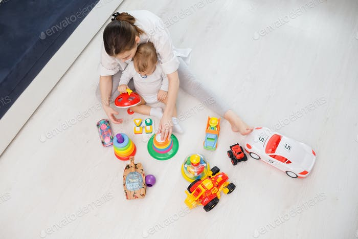 Top view on woman's and child playing with toys wooden on floor