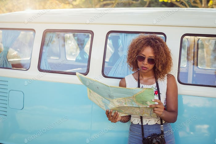 Woman leaning on campervan and looking at map