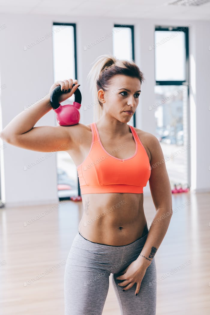 Young fitnesswoman training with a kettle