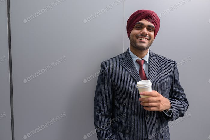 Indian businessman with turban outdoors in city holding coffee cup