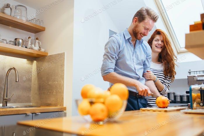 Couple making orange smoothie in kitchen