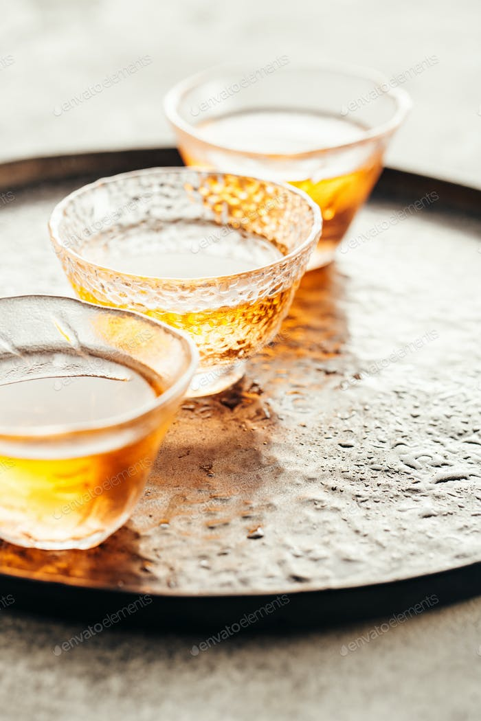 Freshly brewed tea in small glass cups on a tray.