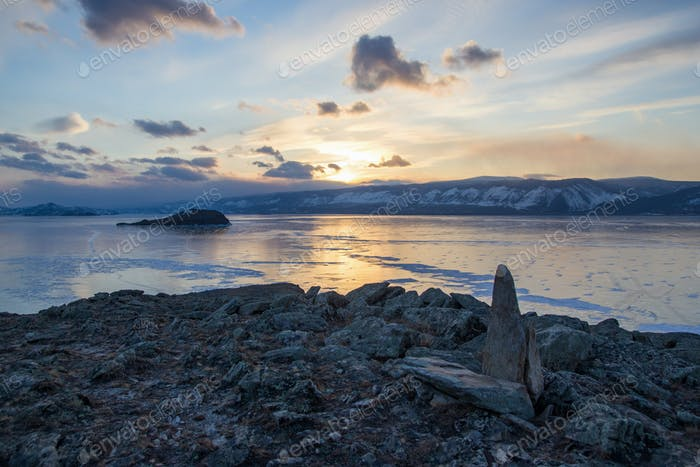 view of lake with ice surface and rocks formations on shore on sunset ,russia, lake baikal