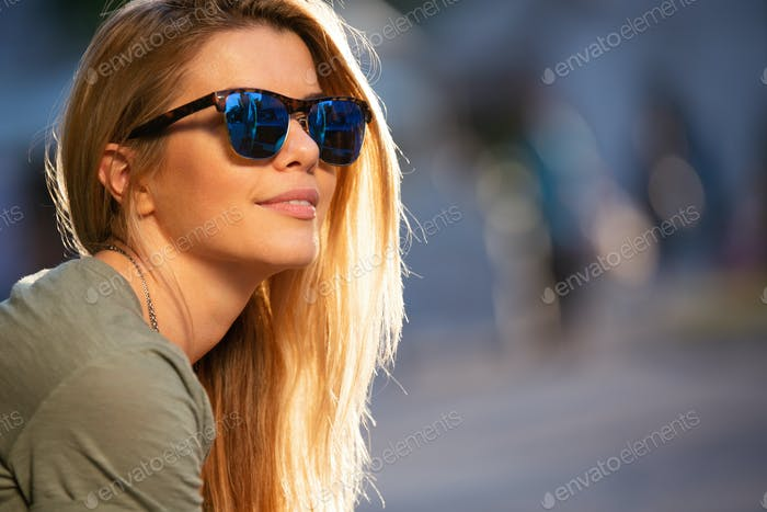 Portrait of young smiling woman in sunglasses