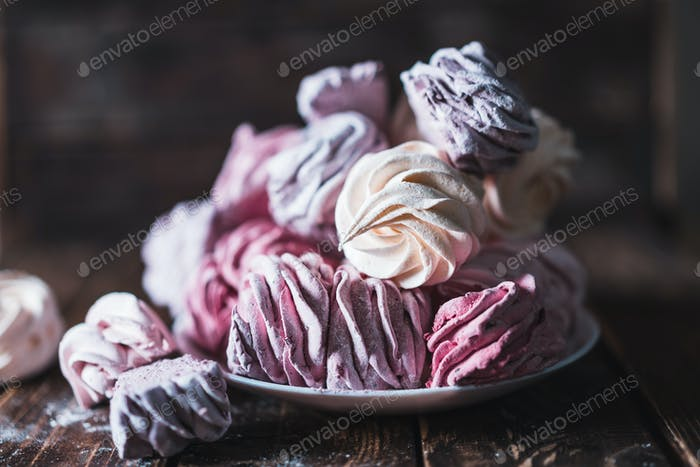 Apetitoso céfiro multicolor en un plato sobre una mesa de madera.
