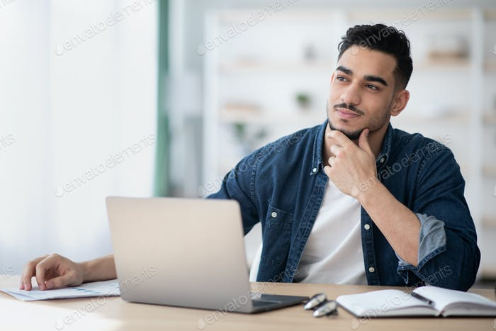 Dreamy young man sitting at office, looking at copy space