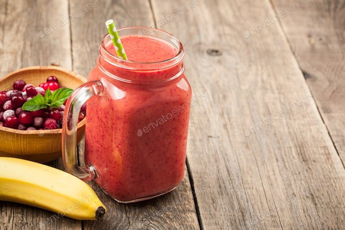 Banana-cranberry smoothie mug and ingredients on wooden table