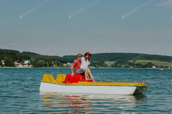 Portrait of smiling couple in love having fun pedal boating.