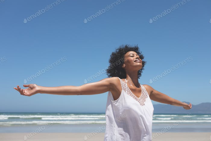 Woman standing with open arm at beach on a sunny day