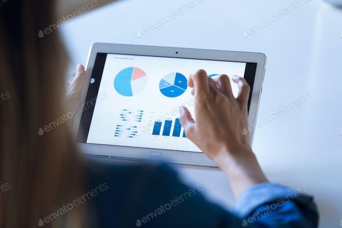 Ziemlich junge Geschäftsfrau, die mit digitalem Tablet im Büro arbeitet.