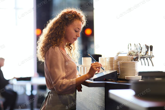 Pensive waitress adding order in restaurant POS