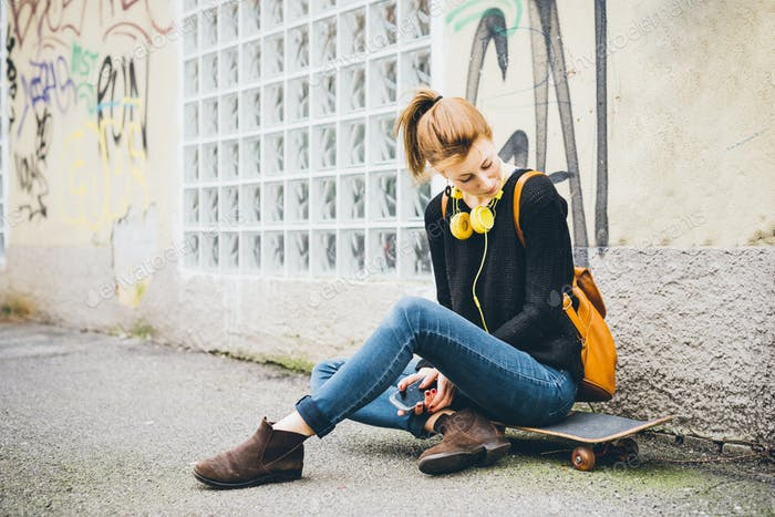 Young beautiful caucasian woman skater sitting on her skate with