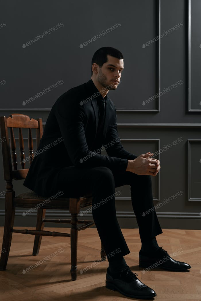 Young handsome businessman in black shirt and black suit