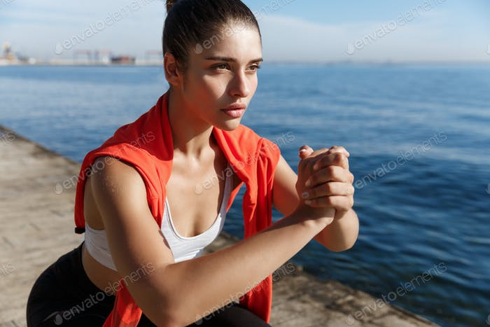 Close-up of confident and focused fitness woman looking at the sea, doing squats and workout on