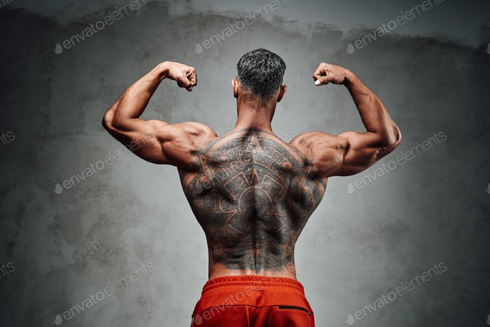Embossed and tattooed fitness couch posing in a studio while standing backwards, showing muscles