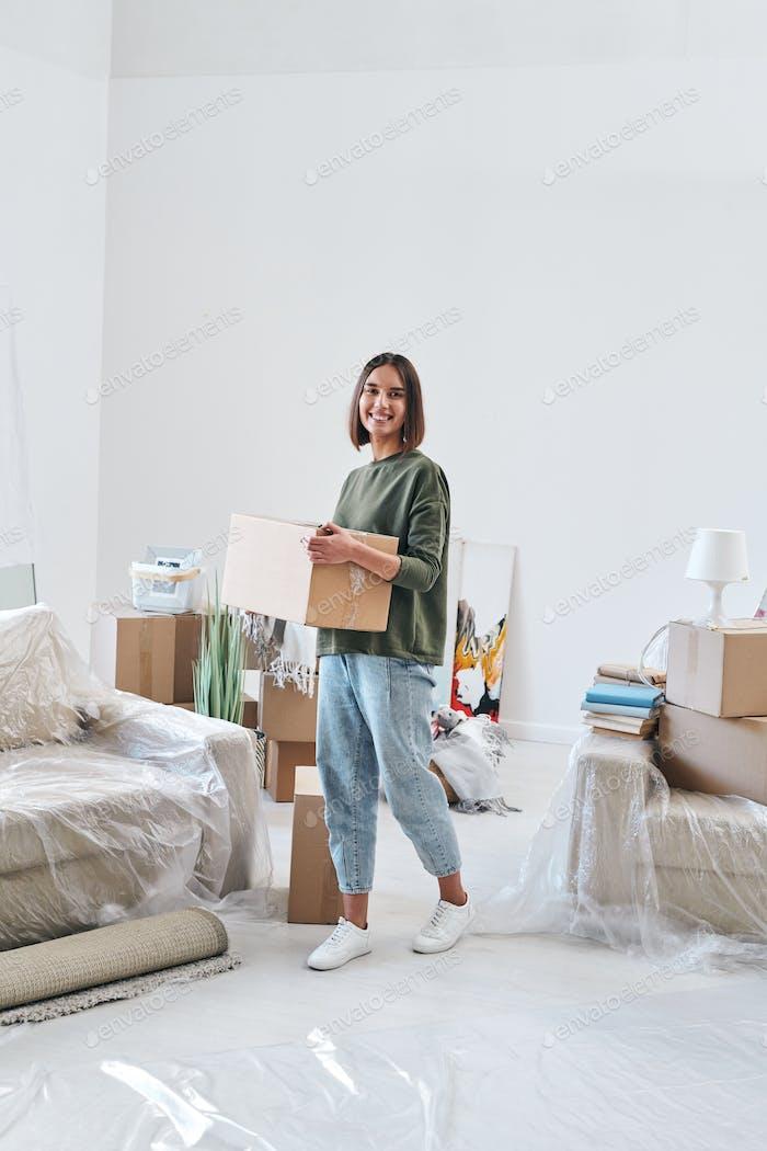 joven mujer alegre en casualwear caja de transporte mientras se mueve a lo largo de la habitación